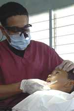 Little boy in dentist's chair getting his teeth examined by the dentist